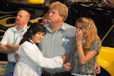 Winner Robert Snyder, flanked by his wife, Sylvia, and his daughter, Savannah, in front of the prize Volvo VNL 670, joins the audience in watching a video about his family.