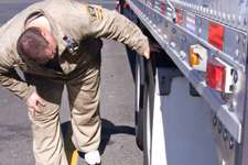 An Oregon Department of Transportation inspector checks tires during a truck inspection. (Courtesy Oregon Department of Transportation)