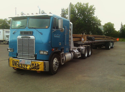 "Dan Wieting was hauling 80-ft. bridge beams with his beautiful, ""trusty old 1987 Freightliner"" cabover ""from Roseville to Tofte, Minn.,"" when he sent in this picture. He added, ""I hung the beam 10 feet over on the front and 22 feet over on the rear."""