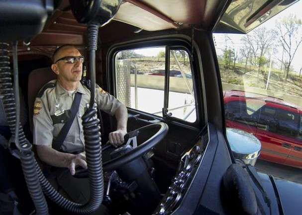 In this photo from the Chattanooga Times Free Press, Tennessee State Trooper pilots the truck used by highway patrolmen to look for motorists breaking driving laws.