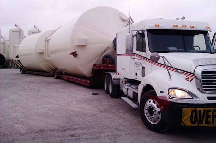 "These lowboy doubles loaded with portable grain bins bound for Beach N.D., says driver Micky Conard, measured 16 feet wide, 18 high, and with an overall length of 95 feet. Conard drives for ""Meridian Manufacturing out of the Storm Lake, Iowa, plant."""