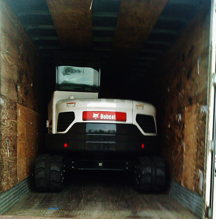 """John Burnett ultimate fit """"two rubber-backed trackhoes"""" snugly in this van trailer."""