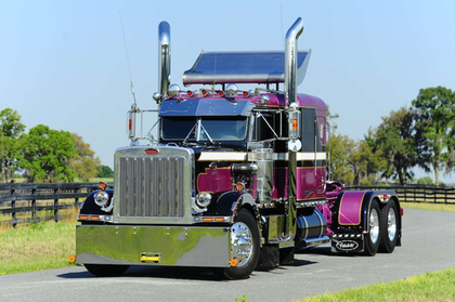 Among the Pete's unique features is the differing color treatment on the hood, cab and sleeper roofs, which unlike most striped-up rigs don't match. While the hood is base black, the roofs above the cab and sleeper are purple – the dark metallic violet Ronnie Adams and company chose for the Adams Motor Express flagship rig.