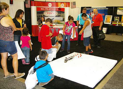 Kids try to back a remote controlled truck at the JBS booth at the Great American Trucking Show in Dallas