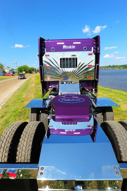 Driver Brent Pecarski keeps the Pete 388's Violet Effect paint job looking bright, washing and polishing and painting the frame rail that was nicked by gravel.