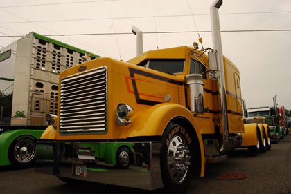 """Iowa-based independent hog hauler Ron Brubaker was showing this """"One of a Kind"""" 1993 Peterbilt, which the owner-operator spec'd as a short hood in October 1992 and has owned ever since. He's thought of dubbing it """"never finished,"""" though, given mods continue to this day. In addition to custom engineering work to turn it into an extended hood, lately Brubaker's been hard at work on the interior with a new tile flooring job and some alligator-skin touches around the bases of the seats, among other things."""