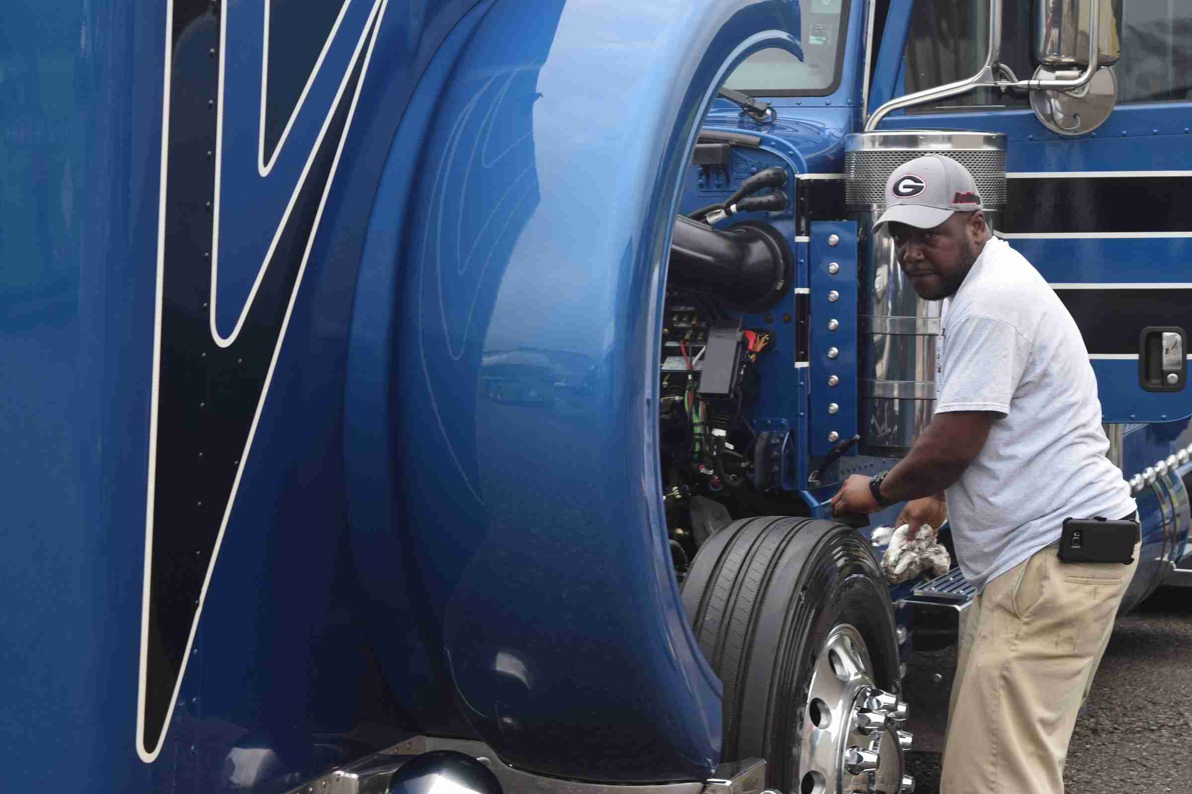 Warren Wiseman, driver for Eric Turner's Atlanta-based Turner Transport small fleet, putting the finishing touches on Turner's 2015 Peterbilt glider, showing with an open car haul trailer.