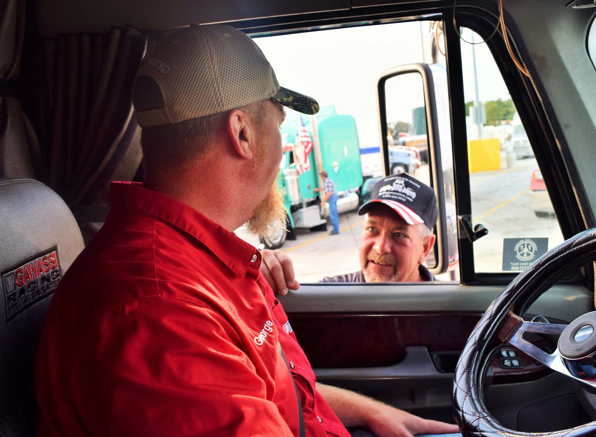 Navy veteran George Parker (left) talking to Air Force vet Jerry Novak from behind the wheel of his well-known Freightliner Coronado.