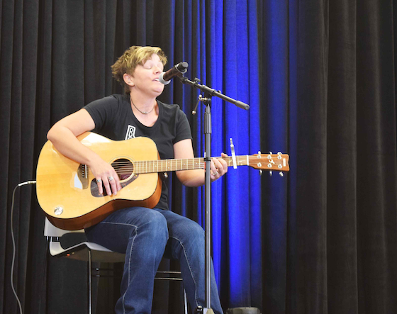 Mandi Jo Pinheiro playing guitar and performing a song on stage