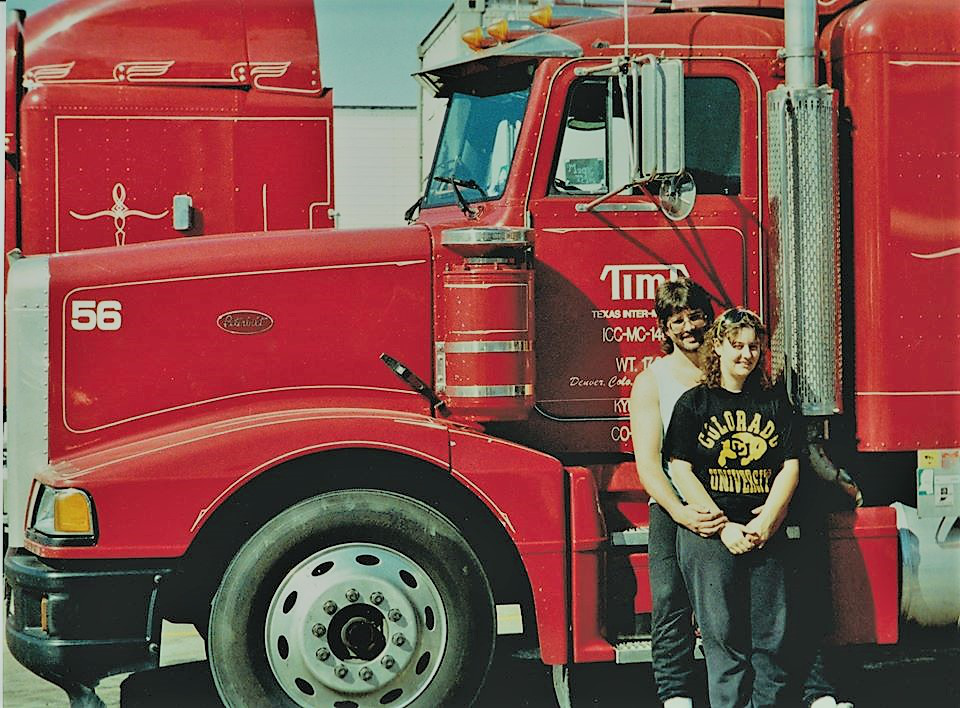 Danny and Cindy George standing in front of a red semi-truck