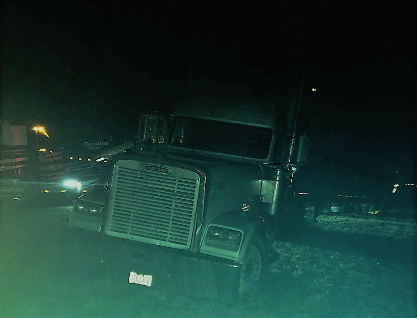semi truck stuck on a muddy median at night