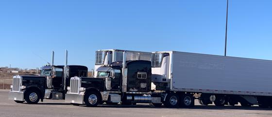 2 semi trucks parked beside each other
