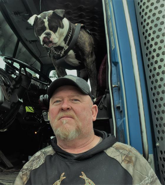 Rob Goodwin with american bulldog in semi truck