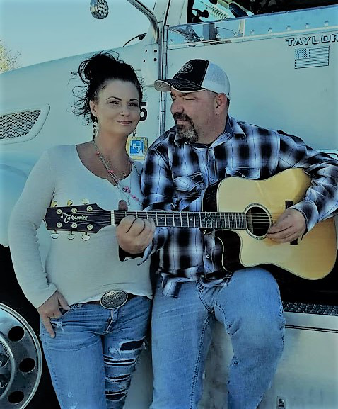 Taylor Barker holding his guitar next to his wife, Cherie, and semi-truck