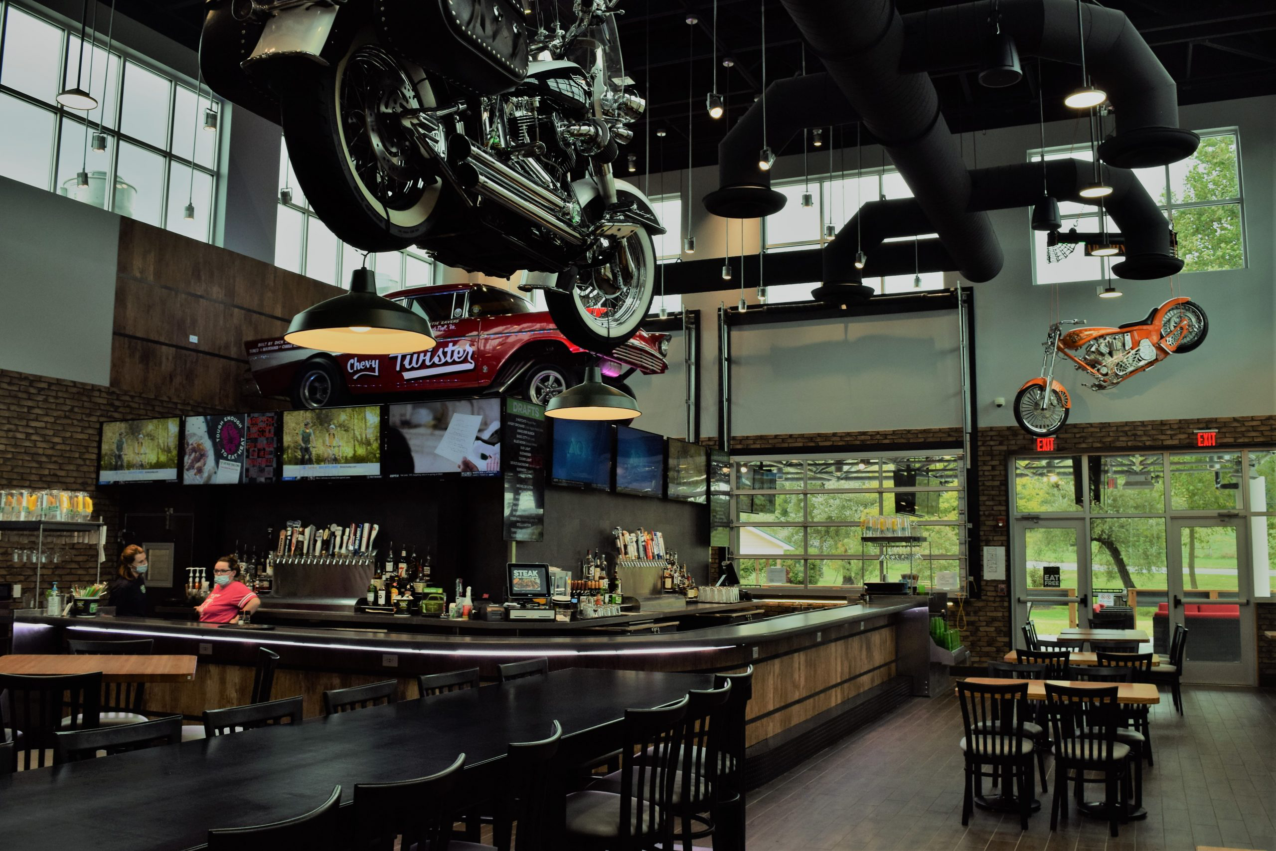 A drag car hanging above the bar and motor cycle hanging over indoor seating