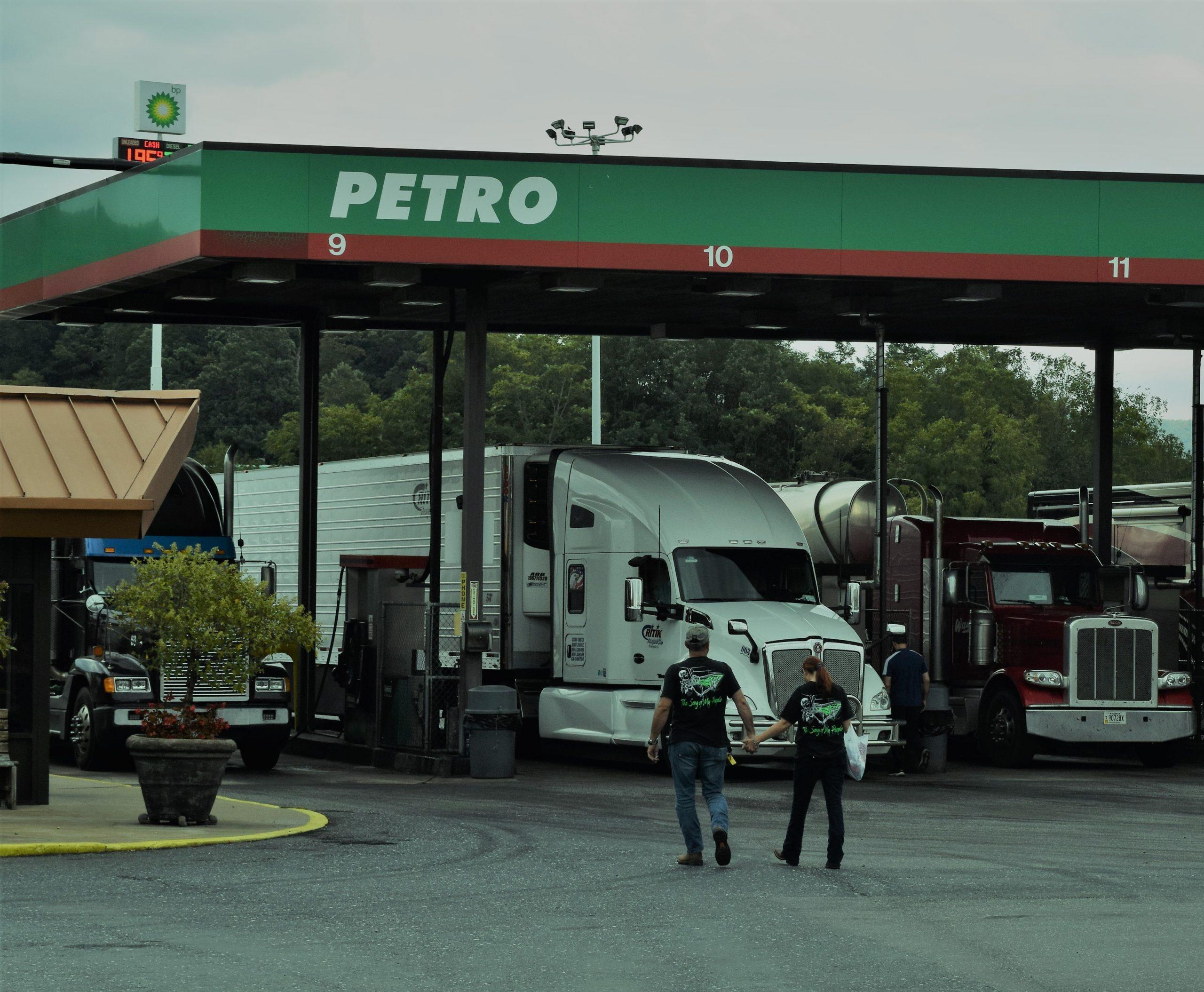 Couple holding hands walking towards Petro fuel pumps