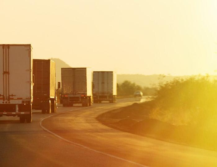 Semi trucks driving along highway